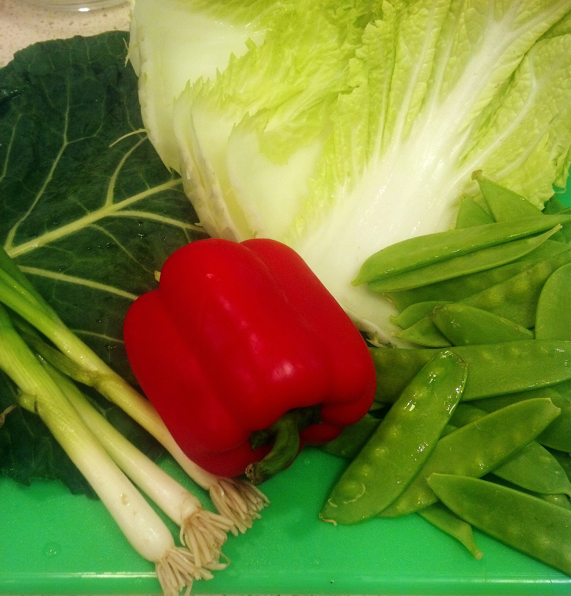 Collard greens, Napa cabbage, red bell peppers, snow peas and scallions ready to julienne for salad