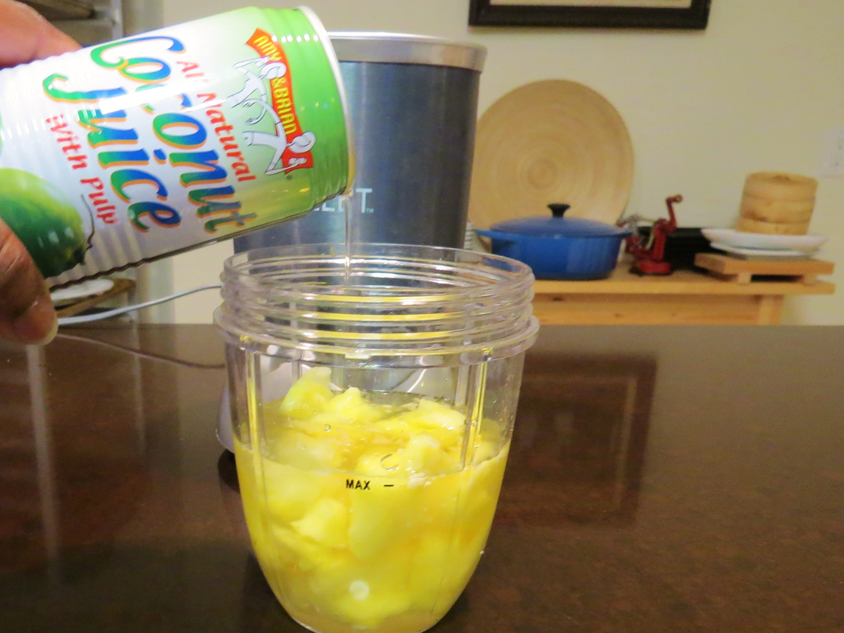 Put Frozen pineapple chunks into the Nutribullet cup up to the fill line.  Pour in Chilled coconut juice