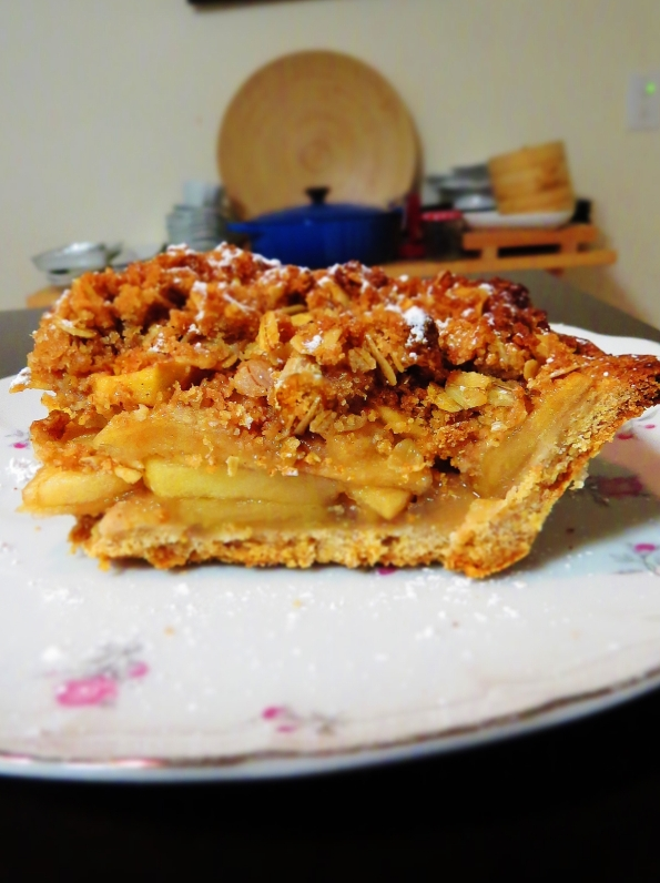 A slice of homemade apple pie with whole wheat pastry crust and oatmeal crunch topping